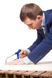 Businessman with a saw. Office worker saws board . the irony of a profession carpenter Royalty Free Stock Images