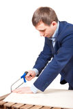 Businessman with a saw. Office worker saws board . the irony of a profession carpenter Royalty Free Stock Photos