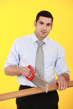 Businessman sawing wood Stock Photo