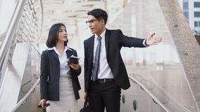 Businessman Say go ahead to businesswoman and compact size hand. Close up Asian young businessman open hand to female traveler or businesswoman route inquiry Stock Images