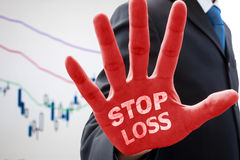 Businessman saying. Businessman in dark gray suit raise his hand in action of stop and words ' stop loss ' on his red palm. Telling how to stop loss from businss Royalty Free Stock Photo