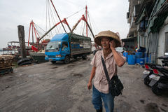 Businessman says on mobile phone in the fishing port in Macau Royalty Free Stock Images
