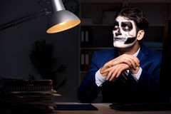 The businessman with scary face mask working late in office. Businessman with scary face mask working late in office Royalty Free Stock Photo