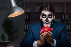 The businessman with scary face mask working late in office. Businessman with scary face mask working late in office Royalty Free Stock Images