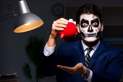 The businessman with scary face mask working late in office. Businessman with scary face mask working late in office Stock Photos