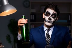 The businessman with scary face mask working late in office. Businessman with scary face mask working late in office Stock Photo
