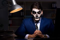 The businessman with scary face mask working late in office. Businessman with scary face mask working late in office Royalty Free Stock Photography
