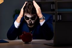 The businessman with scary face mask working late in office. Businessman with scary face mask working late in office Stock Photography