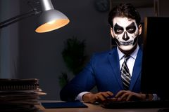 The businessman with scary face mask working late in office. Businessman with scary face mask working late in office Stock Image