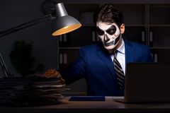 The businessman with scary face mask working late in office. Businessman with scary face mask working late in office Royalty Free Stock Photos