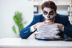 Businessmsn with scary face mask working in office. Businessman with scary face mask working in office Royalty Free Stock Photography