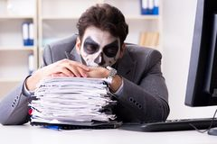 Businessmsn with scary face mask working in office. Businessman with scary face mask working in office Royalty Free Stock Images