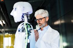 Businessman or a scientist with a robot. Stock Photography