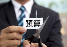 Businessman with scissors cutting label chinese Bu Stock Images