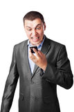 Businessman screaming in cell mobile phone. An angry businessman screaming in cell mobile phone isolated on white background Stock Photography