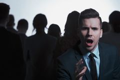 Businessman screaming in a crowd. Young businessman screaming while standing against crowd of people Royalty Free Stock Image