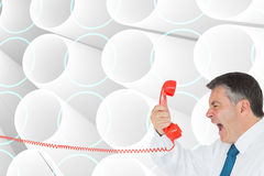 Businessman screaming directly into the handset Royalty Free Stock Images
