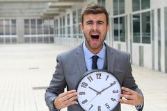 Businessman screaming while holding a big clock.  Stock Photography