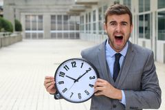 Businessman screaming while holding a big clock.  Stock Photo