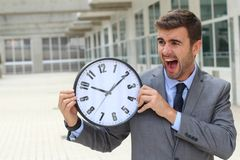 Businessman screaming while holding a big clock.  Royalty Free Stock Photos