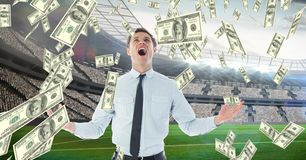 Businessman screaming while looking at money falling representing football corruption Stock Photo