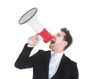 Businessman screaming into megaphone Stock Photos