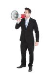 Businessman screaming into megaphone Stock Images