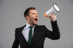 Businessman screaming in megaphone  on grey background. Stock Photos
