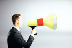 Businessman screaming into megaphone Stock Image
