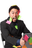 Businessman screaming with notes and laptop Stock Photography
