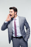 Businessman screaming over gray background Royalty Free Stock Photo