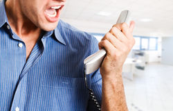 Businessman screaming at the phone. Angry businessman screaming at the phone Stock Images