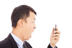 Businessman screaming  into  smart phone over white. Background Stock Photography