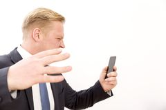 Businessman screaming while talking by phone. Blond Businessman screaming while talking by phone and hand shaking Stock Images