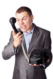 Businessman screaming in telephone receiver. An angry businessman screaming in telephone receiver isolated on white background Royalty Free Stock Photography