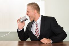 Businessman screaming in tin cans phone. Young Businessman Screaming In Tin Cans Phone At Desk Stock Image