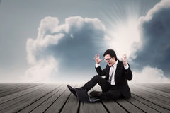 Businessman screaming under clouds Stock Photo
