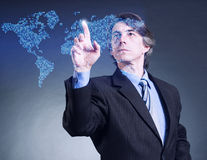 Businessman at the screen with a map. Royalty Free Stock Image