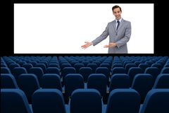 Businessman on screen presenting at blank  in front of 3d empty chairs Royalty Free Stock Images