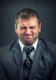 Businessman with screwed-up eyes Stock Image