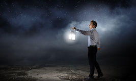Businessman in search in darkness. Young businessman walking with lantern in darkness Royalty Free Stock Images