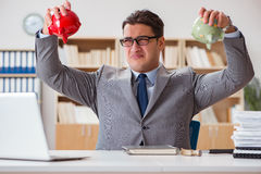 The businessman in search of his savings with piggy bank Stock Images