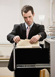 Businessman searches through file drawer Royalty Free Stock Images