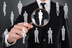 Businessman searching candidate with magnifier. Midsection of businessman searching candidate with magnifying glass over gray background stock photography