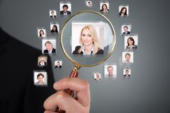 Businessman searching candidate with magnifying glass. Cropped image of businessman searching candidate with magnifying glass over gray background stock photography