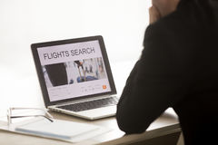Businessman searching cheap low cost business flight on laptop,. Businessman using laptop for searching cheap low cost business flight, choosing airfare deal royalty free stock photo