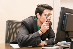 Businessman searching through magnifying glass in Stock Photo