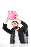 Businessman searching money in piggybank. Royalty Free Stock Photography