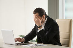 Businessman searching way out from difficult situation. Tired businessman at desk with laptop searching way out from difficult situation. Thoughtful stressed Stock Images