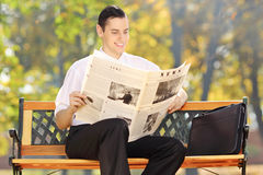 Businessman seated on a bench reading a newspaper in park Stock Photos